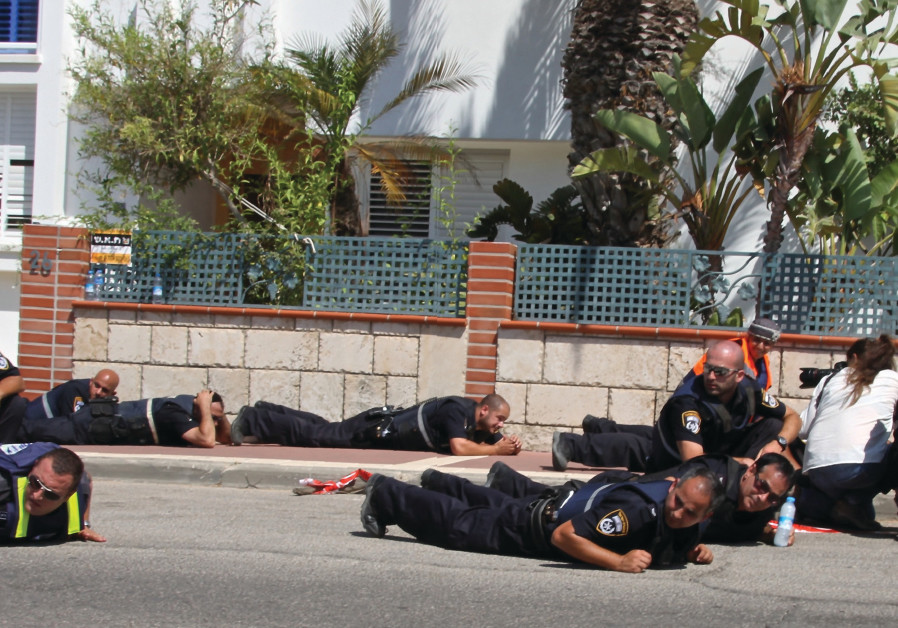 Police officers duck for cover in Sderot as a siren wails in the background during Operation Protect