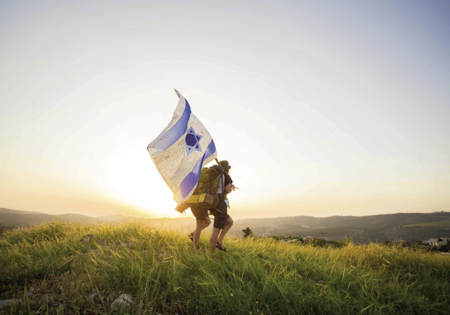 Two hikers carry an Israeli flag near Castel as part of the Masa 70 trek