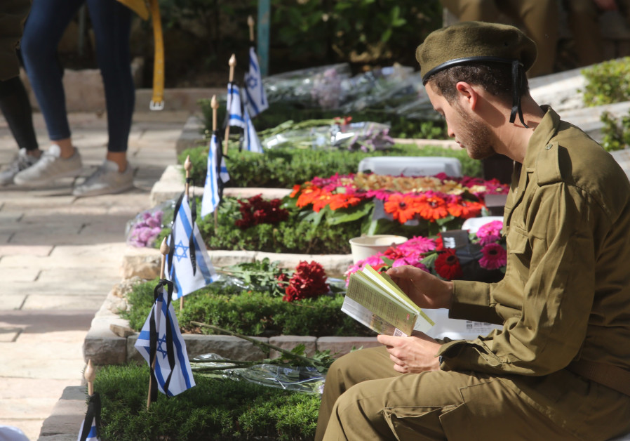 An Israeli soldier sits by a grave on Mount Herzl during Remembrance Day on April 18th, 2018.