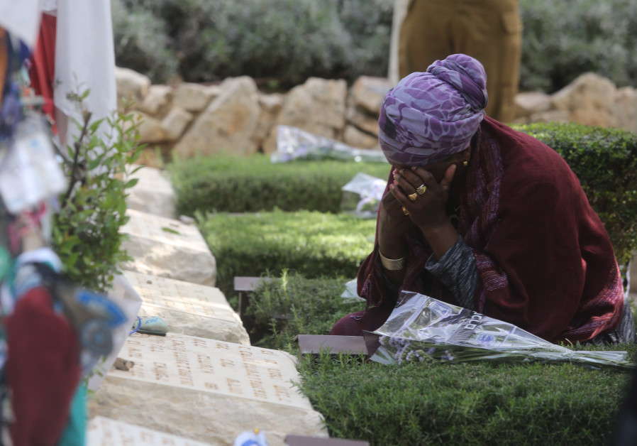 A woman cries while sitting near a grave on Mount Herzl during Remembrance Day on April 18th, 2018.