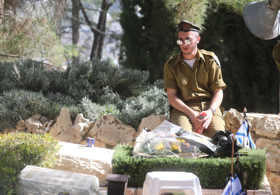A soldiers rests overlooking graves on Mount Herzl on Remembrance Day on April 18th, 2018. (Credit: Marc Israel Sellem/The Jerusalem Post)