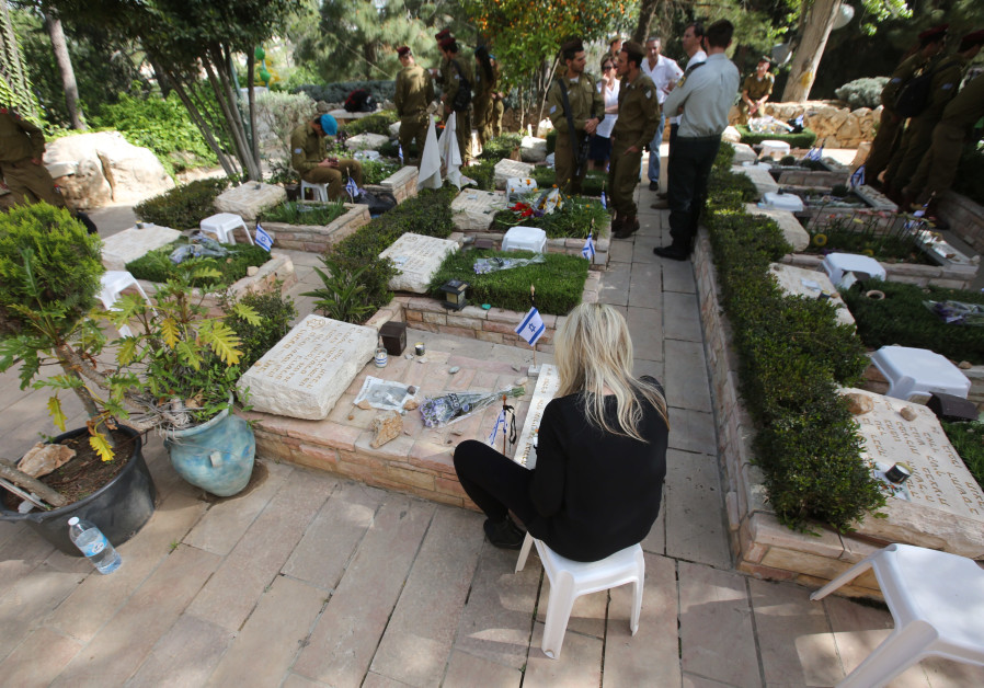 An Israeli sits near a grave during Remembrance Day on April 18th, 2018.