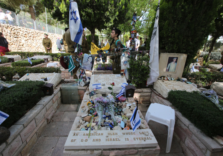The grave of Michael Levin, who was killed at 22 during the Second Lebanon War, is covered in stones and Israeli flags during Remembrance Day on April 18th, 2018. (Credit: Marc Israel Sellem/The Jerusalem Post)