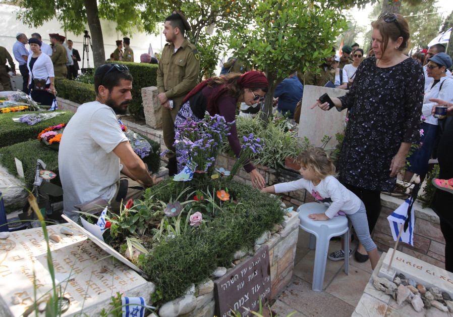 Israelis place a rock on a grave on Mount Herzl during Remembrance Day on April 18th, 2018. (Credit: Marc Israel Sellem/The Jerusalem Post)