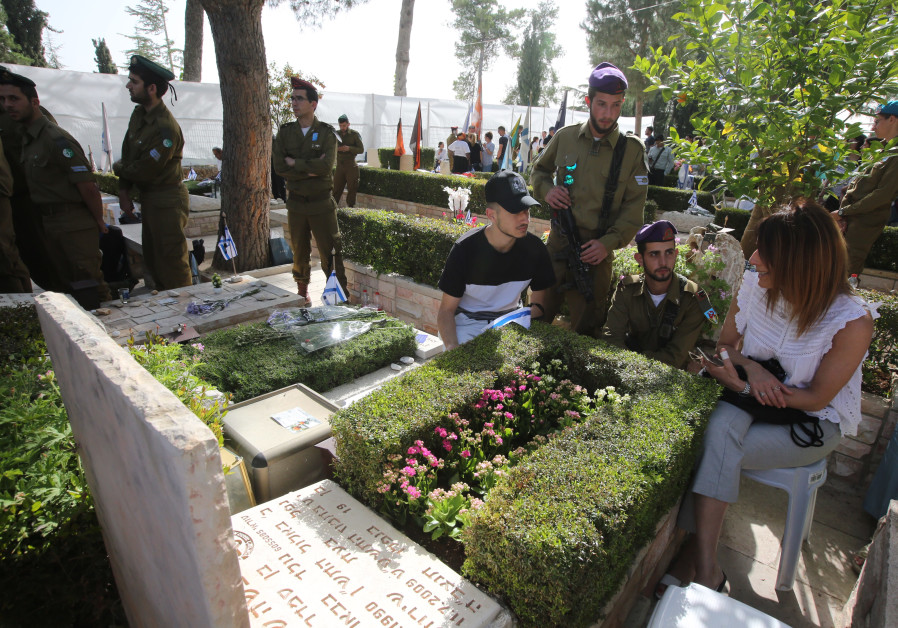 Israelis visit a grave on Mount Herzl during Remembrance Day on April 18th, 2018. (Credit: Marc Israel Sellem/The Jerusalem Post)