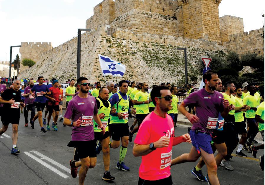 ATHLETES RUN outside the Old City during the eighth International Jerusalem Marathon last month