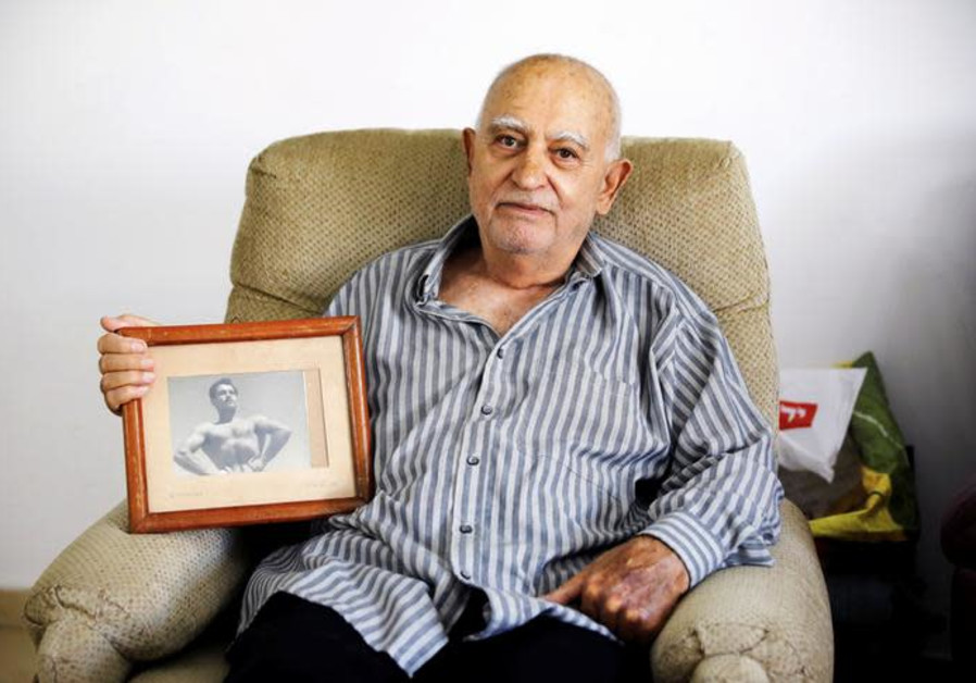 Aharon Ben Hur, 84, who immigrated from Iraq to Israel in 1951, holds an old photo.