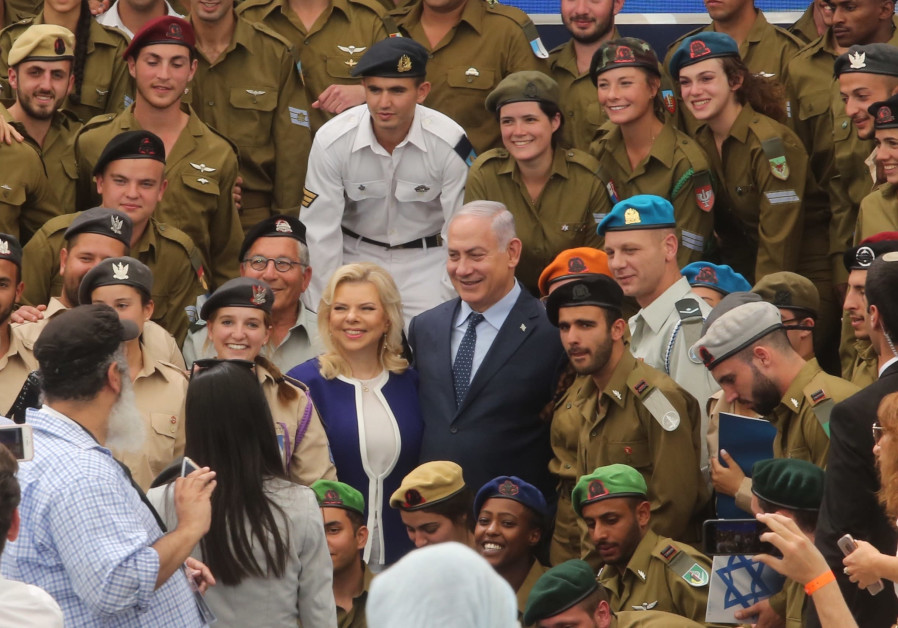Prime Minister Benjamin Netanyahu and his wife, Sara, pose with soldiers during an annual event to celebrate distinguished soldiers on Israel's independence day. (Marc Israel Sellem/The Jerusalem Post)