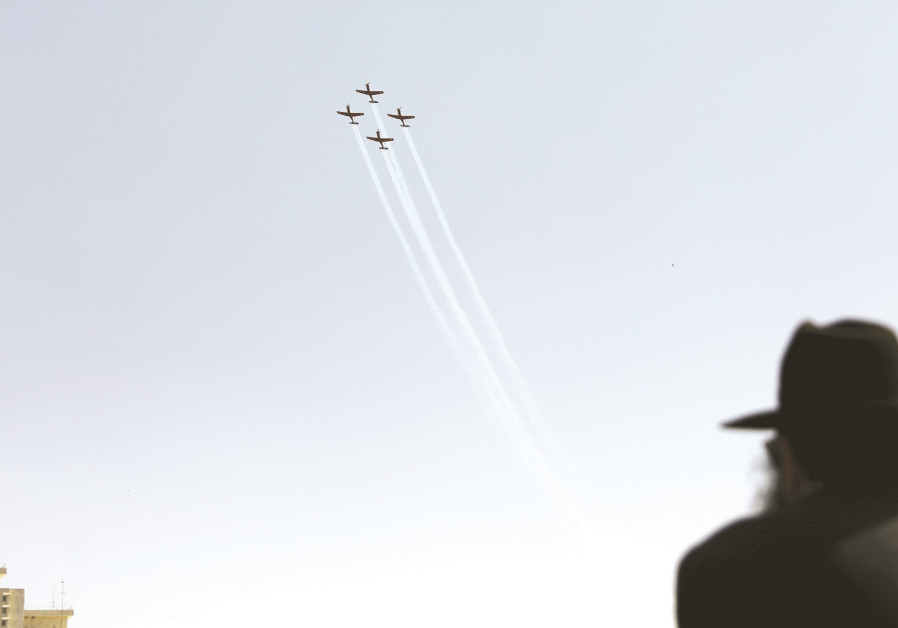 An ultra-Orthodox man watches planes fly overhead.