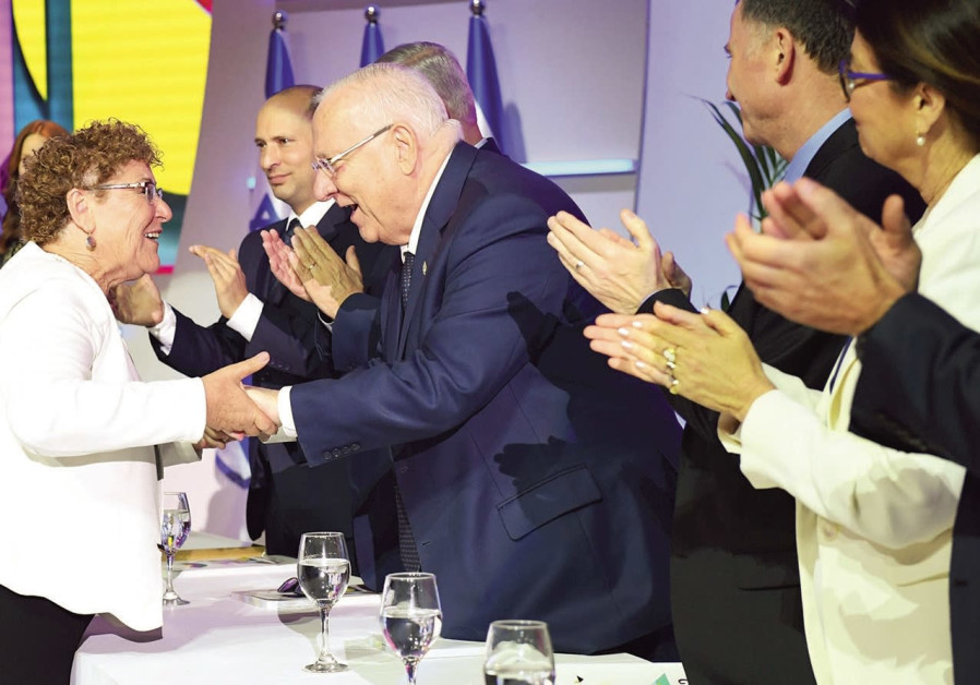 Miriam Peretz (L) shakes hands with Israel President Reuven Rivlin (R).