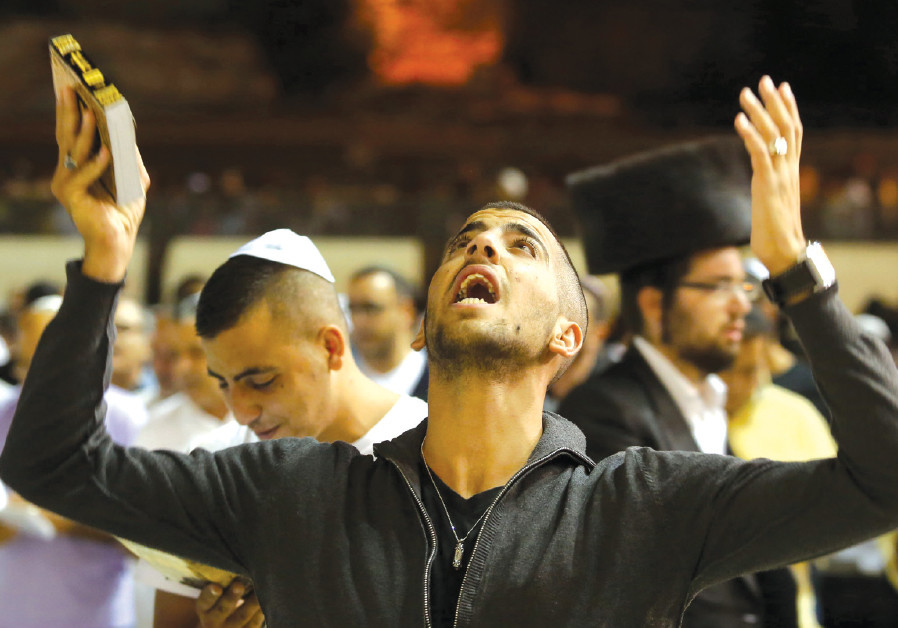 A WORSHIPER prays at the Western Wall