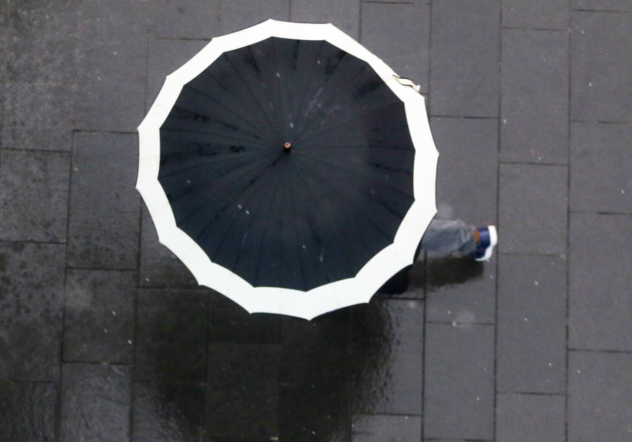 A person walks with an umbrella during a rain storm in Jerusalem, April 25, 2018
