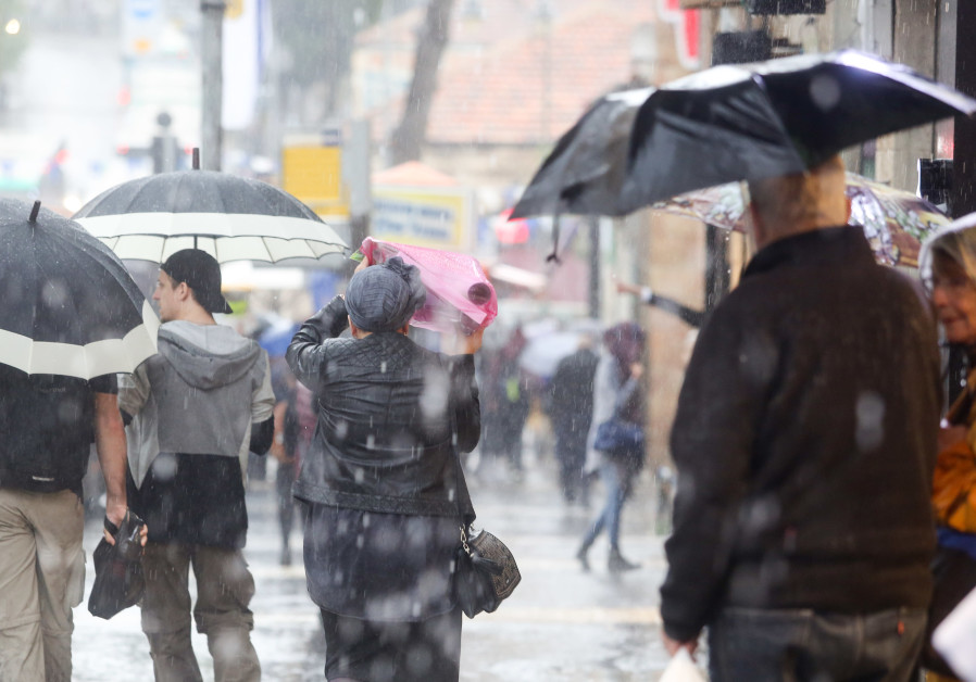 People seek shelter during a rain storm in Jerusalem, April 25, 2018