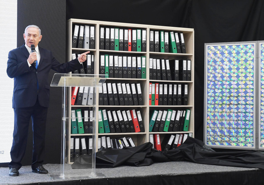 Prime Minister Benjamin Netanahu points to files containing copys of Iranian data.