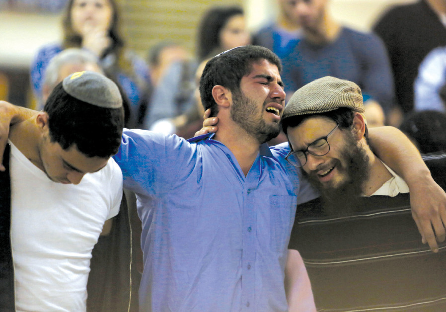 RELATIVES AND friends mourn during a ceremony for Ezra Schwartz at Ben-Gurion International Airport