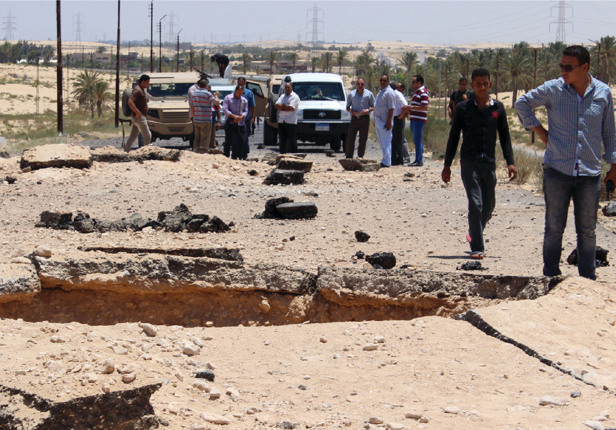 EGYPTIAN SECURITY officials inspect the site of a bomb blast targeted at soldiers on the highway bet