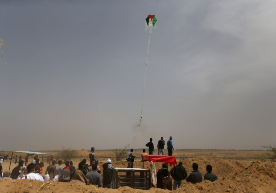 Palestinians set a kite on fire to be thrown at the Israeli side during clashes at a protest
