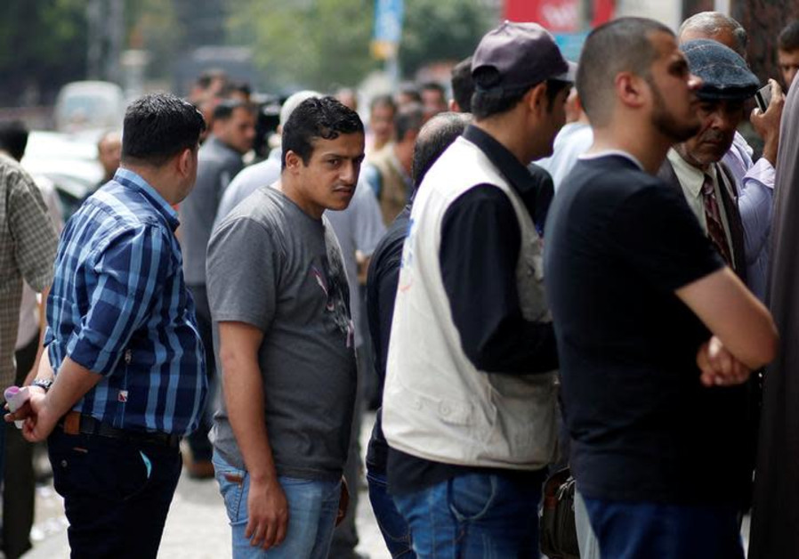 Public servants of the Palestinian Authority queue to receive their salaries outside a bank in Gaza.