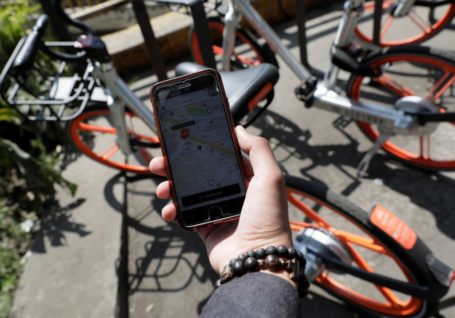 A man holds his mobile phone displaying the Mobike app next to a parked bicycle