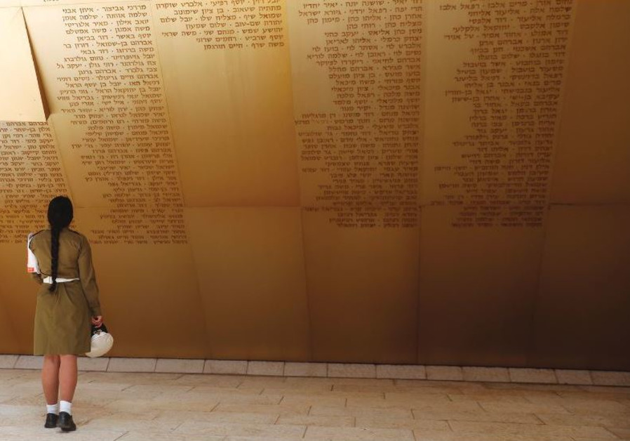 A SOLDIER stands in front of a monument engraved with names of fallen soldiers, ahead of a ceremony