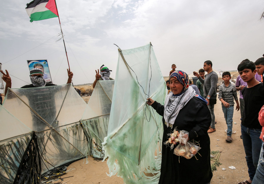 A Palestinian woman walks with a kite as other demonstrators pose before trying to fly them.
