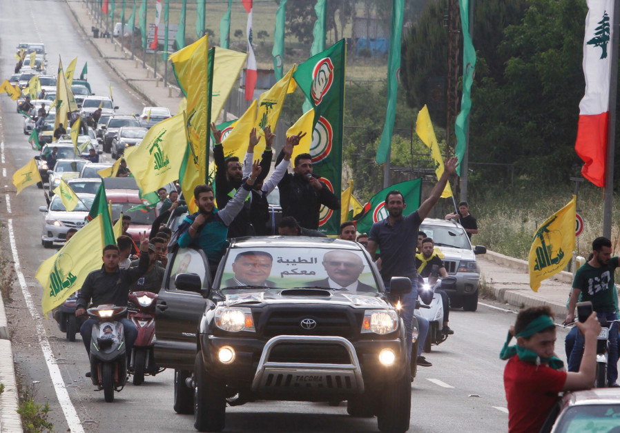 Supporters of Lebanon's Hezbollah and Amal Movement ride in a car in Marjayoun, Lebanonba