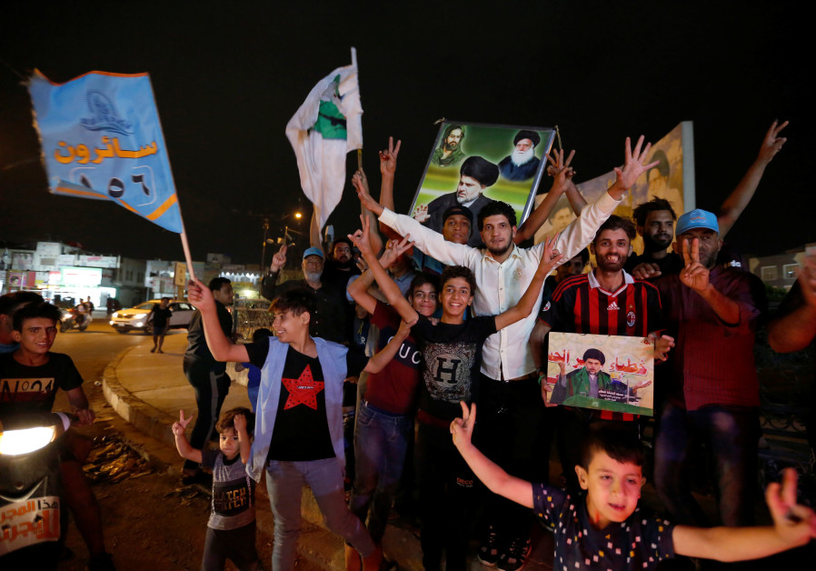 Iraqis celebrate after the closing of ballot boxes during the parliamentary election