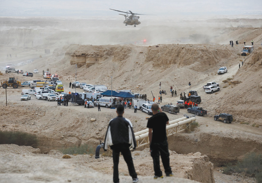 Israeli rescue service personnel operate near the site where 10 Israeli youths were swept away by a