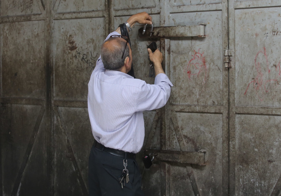A Palestinian in the Old City of Jerusalem closing his shop.