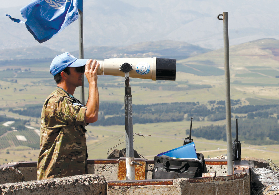 A UNITED NATIONS observer keeps watch over the Syrian border from the Golan Heights, May 2018