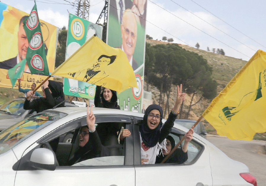 HEZBOLLAH SUPPORTERS gesture out of a car window in Marjayoun, Lebanon, on May 7, 2018