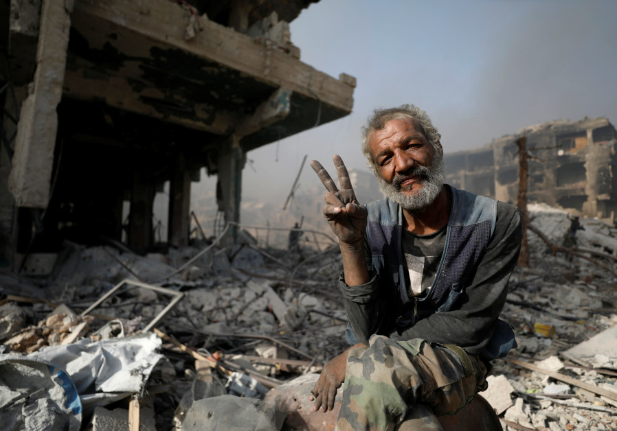 A man gestures as he sits on the rubble of damaged buildings in al-Hajar al-Aswad, Syria May 21, 201