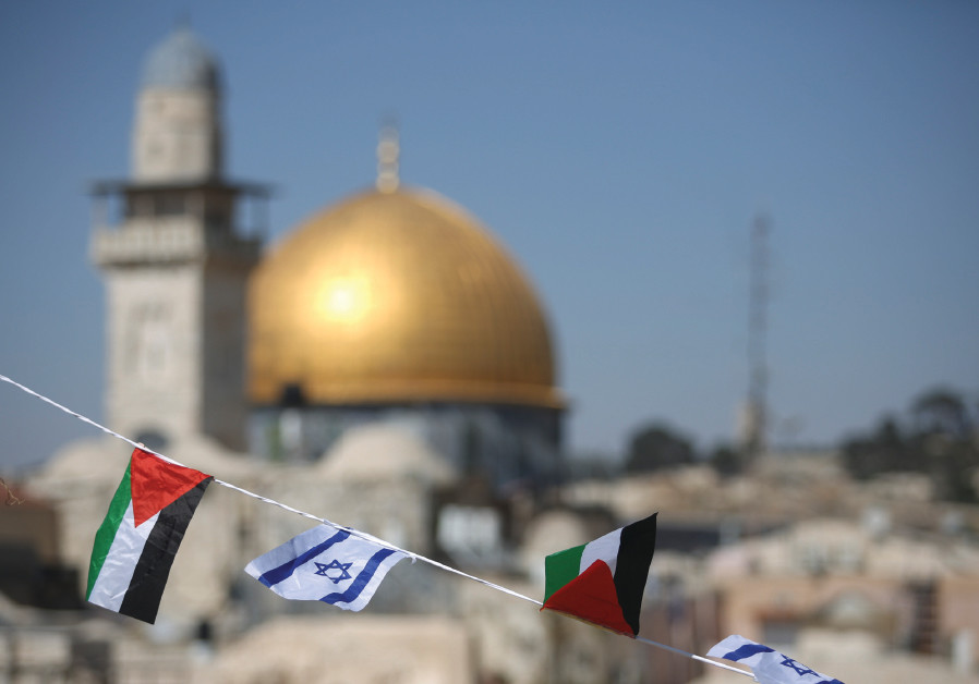 PALESTINIAN AND Israeli flags fly over the Western Wall and the Dome of the Rock