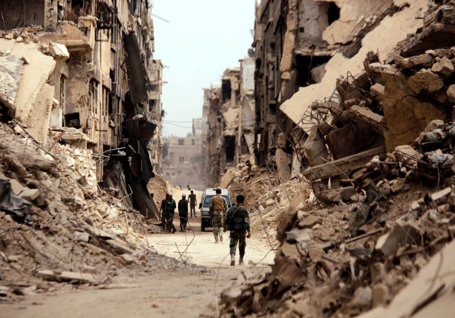 SYRIAN SOLDIERS walk past damaged buildings in the Yarmouk Palestinian refugee camp in Damascus.