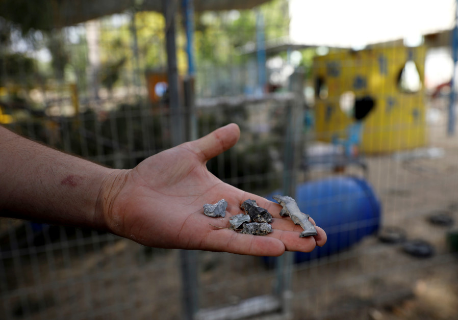 A man holds shrapnel from mortar shells fired from the Gaza Strip that landed near a kindergarten