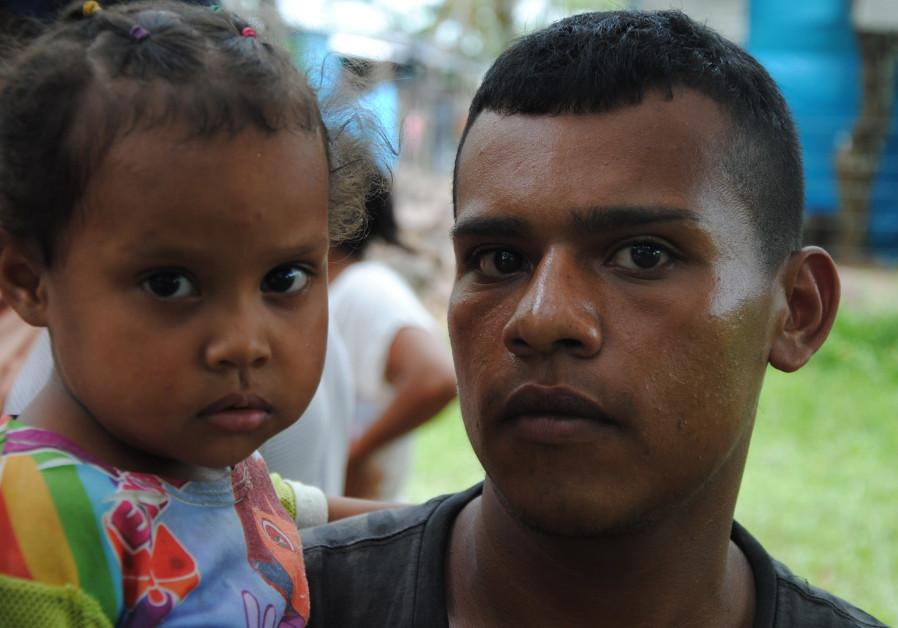 Ivan Carranza, 24, with his daughter, Maikelis, immigrants from Venezuela