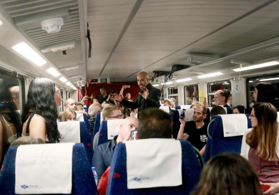 Magician Hezi Dean does magic for passengers on a train ride to Tel Aviv.