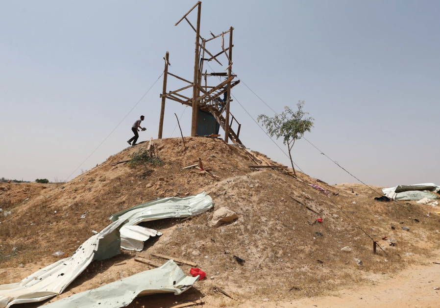 PALESTINIANS INSPECT an Islamic Jihad observation post after it was targeted by an Israeli tank