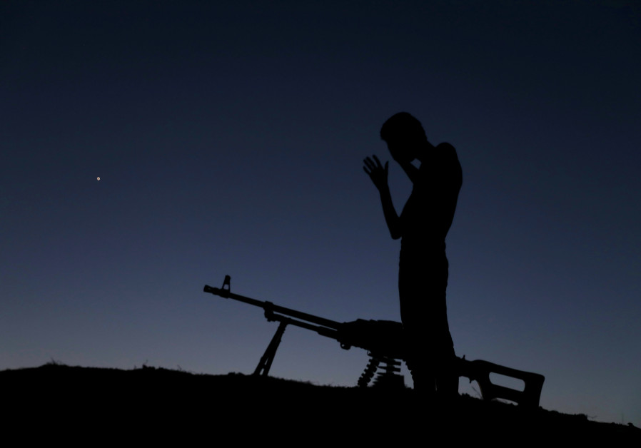 A Free Syrian Army fighter prays after eating his iftar (breaking fast) meal during the holy month