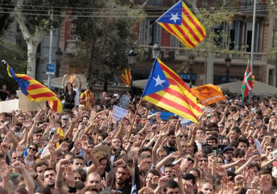 People shout as Esteladas (Catalan separatist flags) flutter during a protest the day after the banned independence referendum in Barcelona, Spain October 2, 2017. (Enrique Calvo/Reuters)