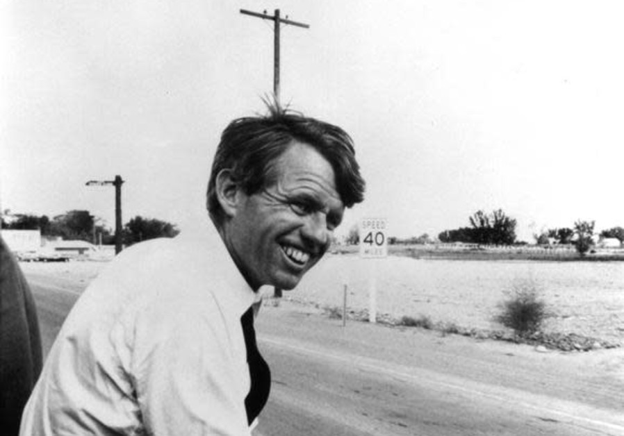 Robert F. Kennedy sits alongside the motorcade in this 1968 file photograph.