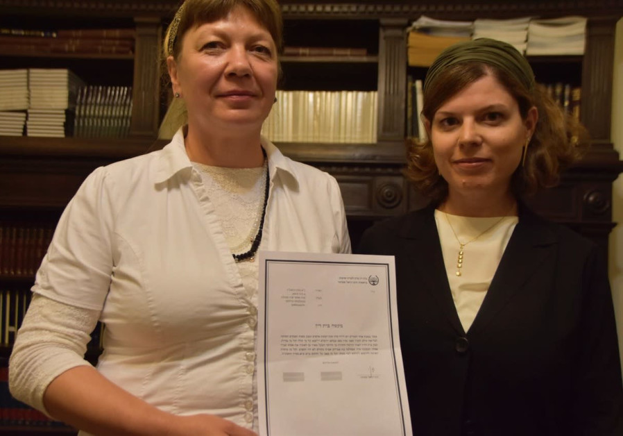 Zvia Gordestski (left) holding the rabbinical court document freeing her from her marriage