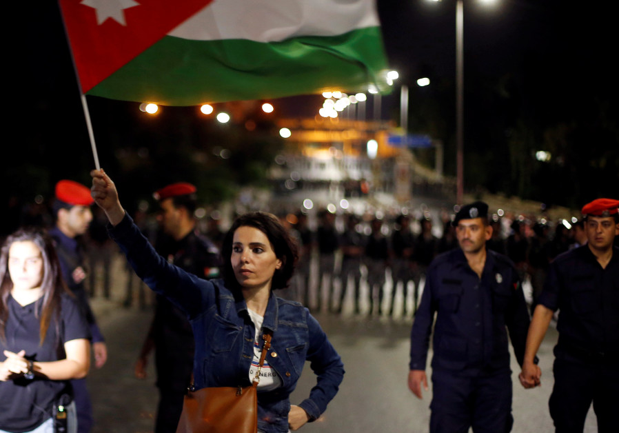 A protester holds up a Jordanian national flag during a protest in Amman, Jordan June 4, 2018.