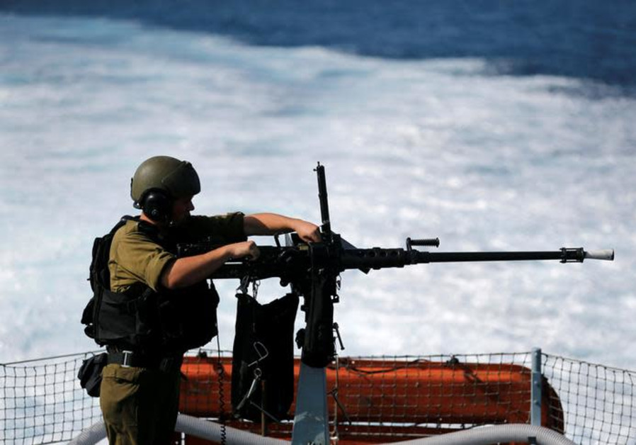 An Israeli soldier from the navy loads a machine gun as he takes part in a drill practicing the defe