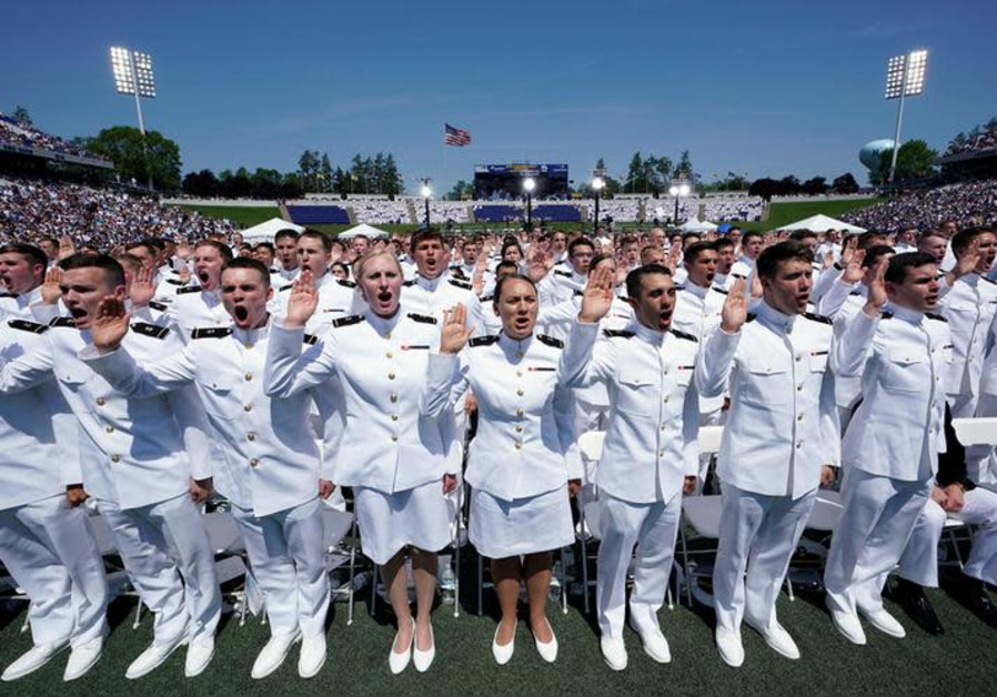 Members of the U.S. Naval Academy graduating class stand to be sworn in during their commissioning a