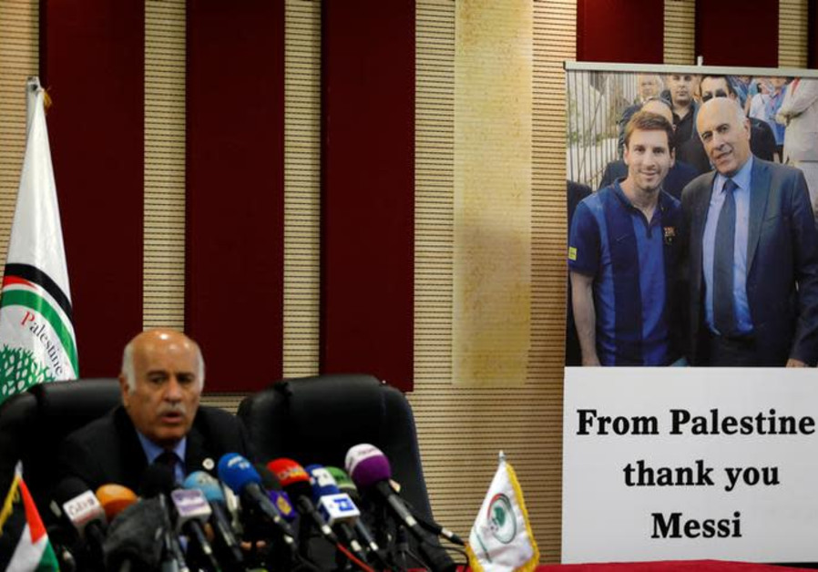 A poster of Palestinian FA chief Jibril Rajoub with Argentina's soccer player Lionel Messi is seen d