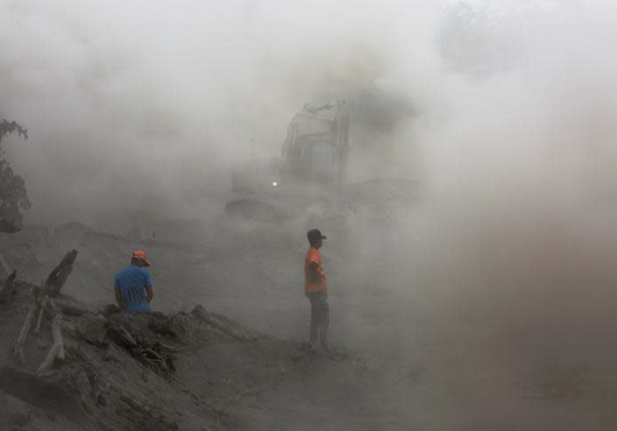 Residents are seen amidst ashes as heavy machinery removes ash from a road at an area affected by th