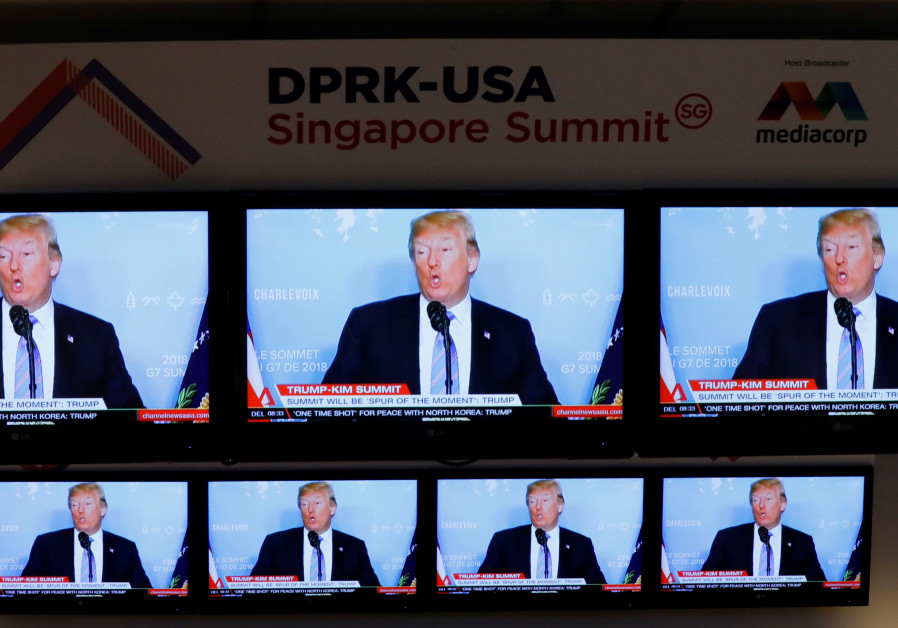 A TV news reports about U.S. President Donald Trump is projected on TV sets at a media center for th