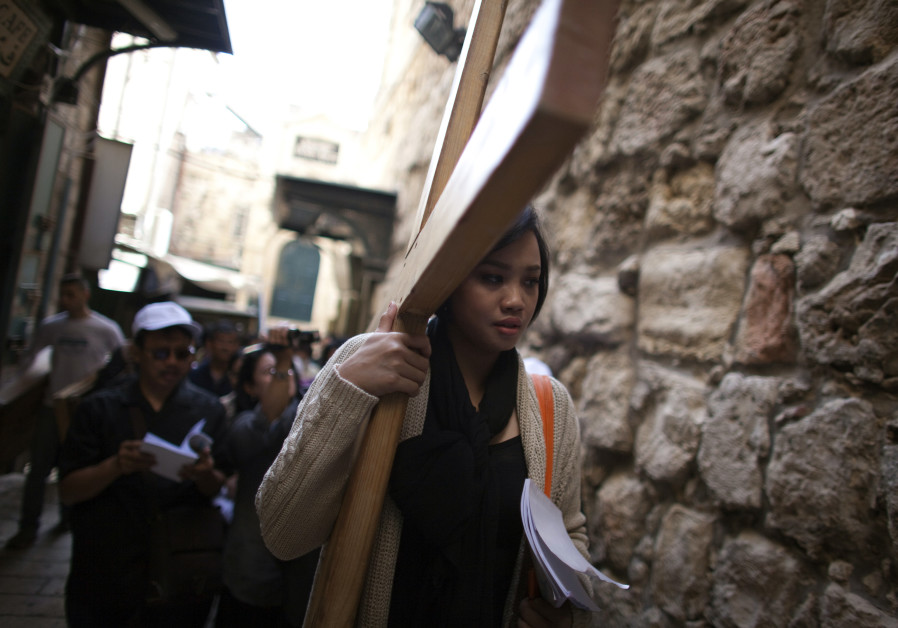 An Indonesian Christian worshipper holds a cross as she walks the Via Dolarosa on Good Friday in Jer