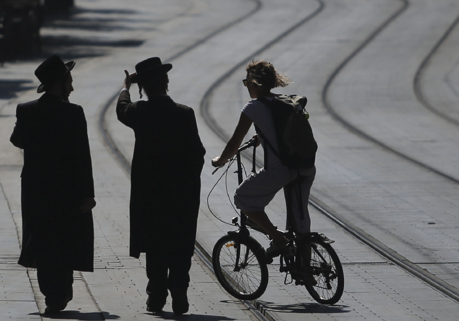 A secular woman cycles in downtown Jerusalem, alongside ultra-Orthodox pedestrians